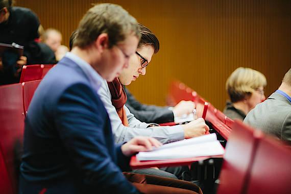 Studierende in einem Hörsaal, in den Bänken sitzend