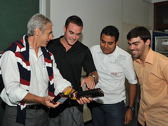 Ein Professor und drei international Studierende besprechen sich und begutachten dabei ein technisches Bauteil.